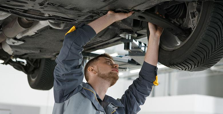 Handwerker arbeitet am Unterboden eines Autos