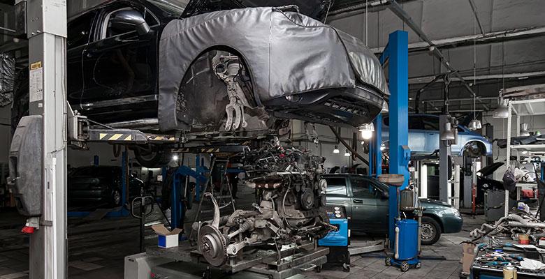 KFZ-Werkstatt mit Auto auf einer Hebebühne und ausgebautem Motor