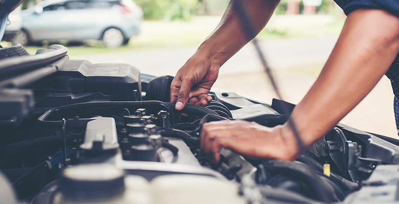 Mechaniker-Hände in einem Motorraum