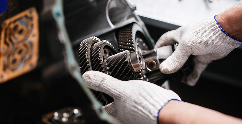 Behandschuhte Hände arbeiten an einem Getriebe