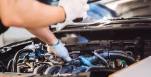Mechaniker beugt sich über geöffneten Motorraum