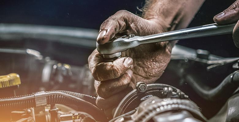 Ölverschmierte Hand mit Schraubwerkzeug in einem Motorraum